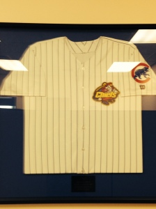 Framed #31 jersey hanging in Chiefs front office with Maddux plaque